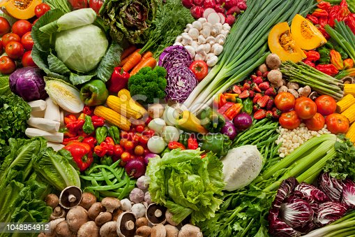 Colorful composition of assorted vegetables: tomato, lettuce, cabbage, onions, bell peppers, strawberries, broccoli, corn and mushroom among others. Full frame. High angle view. Horizontal. Studio photography. No people. Healthy eating concept. Organic and fresh food concept.