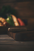Assorted vegetables with chopping board and knife shot in dark moody light