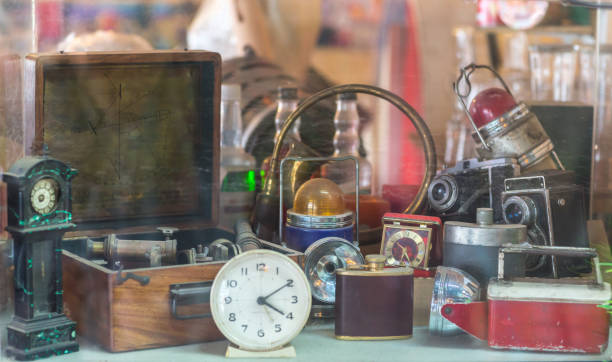 Assorted vintage items, clocks, cameras, flasks, sextant, lamps behind shop window. A display of interesting, old fashioned items and trinkets in a pawn shop. antique stock pictures, royalty-free photos & images