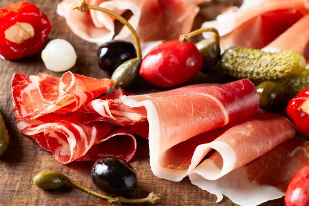 Assorti von in Scheiben geschnittenen Marmelade, Salami, Schinken mit Oliven, Kapern – Foto