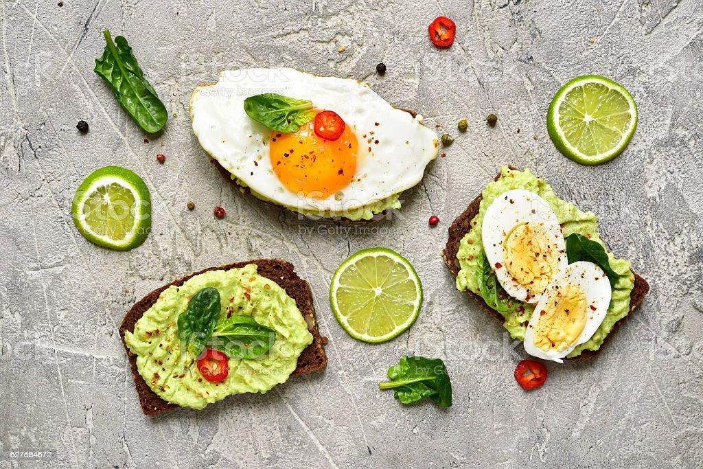 Assortment of avocado toasts. stock photo