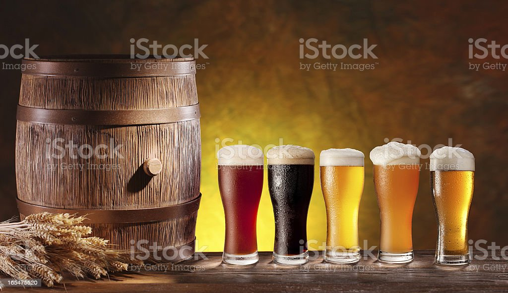 Assortment of beer glasses with a wooden barrel. royalty-free stock photo