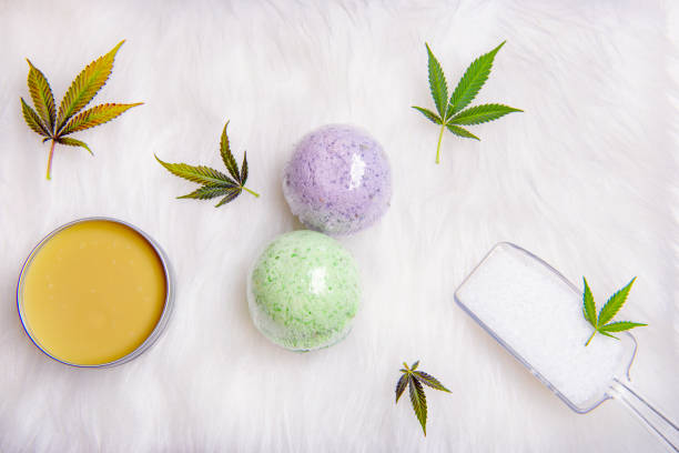 Assortment of cannabis topicals with bath bombs and marijuana salve over white stock photo