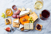 istock Assortment of cheese, grapes with red and white wine in glasses. Marble background. Top view. 1125957536