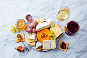 istock Assortment of cheese, grapes with red and white wine in glasses. Marble background. Top view. 1126485210