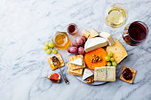 istock Assortment of cheese, grapes with red and white wine in glasses. Marble background. Top view. Copy space. 1189180576