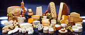 large assortment of international cheese specialities on black background