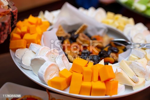 Assortment of cheese around serving dish and dried fruit in the middle