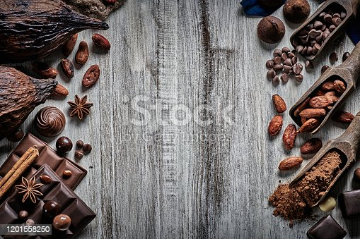 Assortment of chocolate: Candies, Bonbon, chocolate bars, nuts and cacao beans on a white wooden rustic table