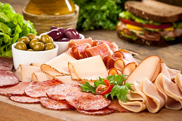 assortment of cold appetizer displayed on rustic wood table - delis stock photos and pictures