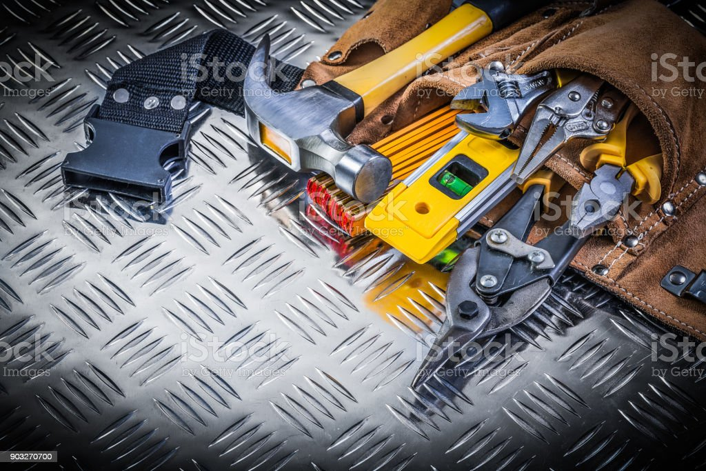 Assortment of construction tooling in leather tool belt on chann stock photo