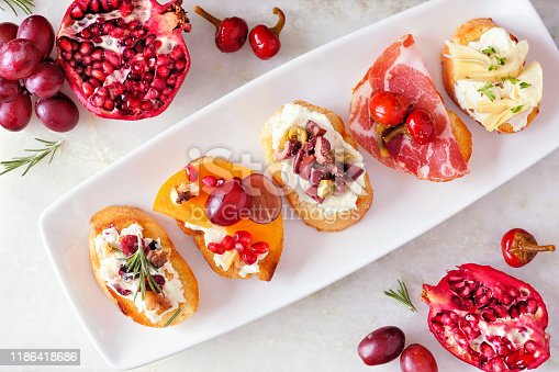 Assortment of crostini appetizers with a variety of toppings. Above view table scene on a bright background. Party food concept.