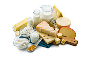 High angle view of a large assortment of most common dairy products shot on white background. The composition includes milk, sour cream, butter, yogurt, Manchego cheese, goat cheese, emmental cheese, Cheddar cheese, Roquefort cheese, Gouda cheese and cottage cheese. Some cheeses are on a wooden cutting board and the milk bottle, eggs and the cottage cheese are sitting on a blue folded tablecloth. Predominant colors are white, yellow and blue. High resolution 42Mp studio digital capture taken with Sony A7rii and Sony FE 90mm f2.8 macro G OSS lens
