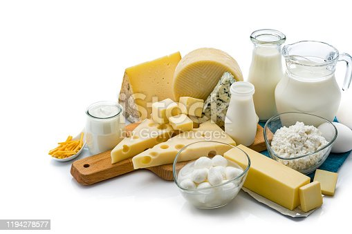 Large assortment of most common dairy products shot on white background. The composition includes milk, sour cream, butter, yogurt, eggs, Manchego cheese, goat cheese, emmental cheese, Cheddar cheese, Roquefort cheese and cottage cheese. Some cheeses are on a wooden cutting board and the milk bottle, eggs and the cottage cheese are sitting on a blue folded tablecloth. Predominant colors are white, yellow and blue. High resolution 42Mp studio digital capture taken with SONY A7rII and Zeiss Batis 40mm F2.0 CF