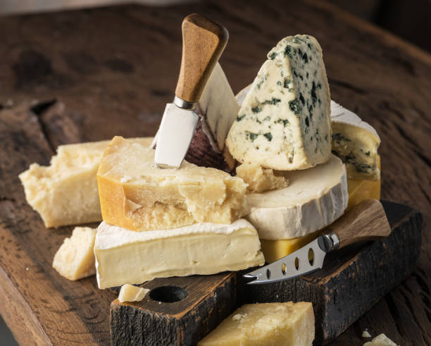 Assortment of different cheese types on wooden background. stock photo