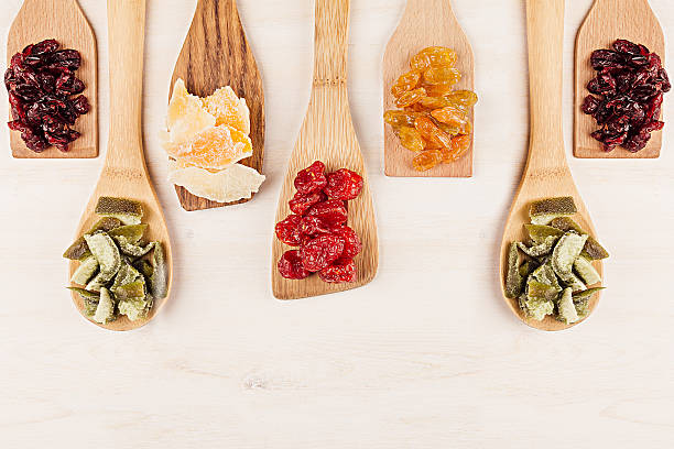 assortment of dried fruits on wooden spoons on white background. - dried fruit stock photos and pictures