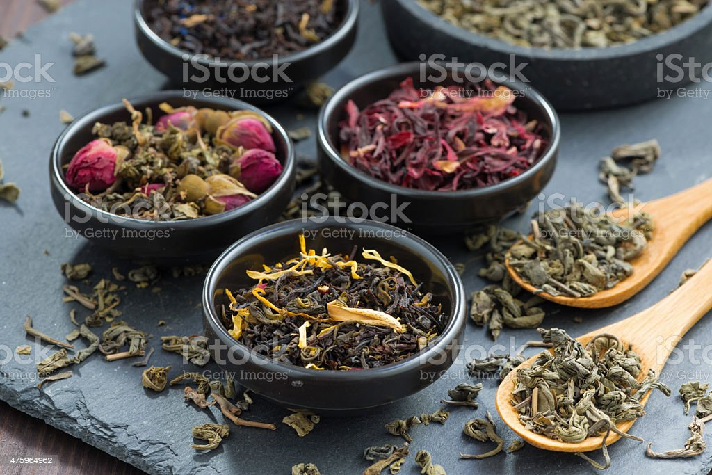 assortment of dry tea in ceramic bowls stock photo