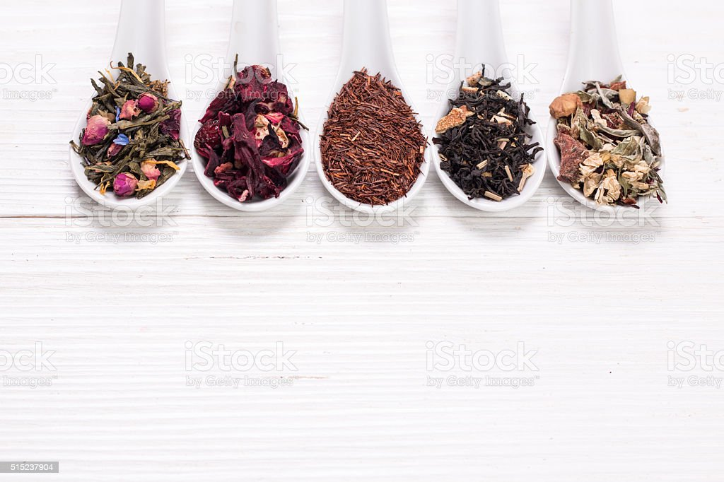 assortment of dry tea on a wooden table,healthy drink stock photo