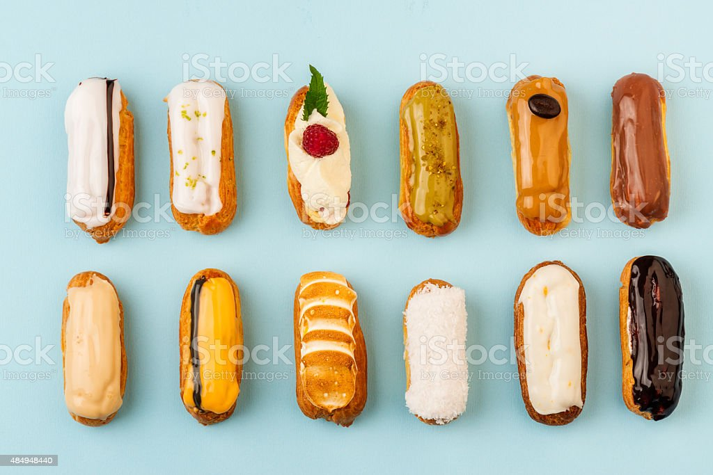 Assortment of eclairs on blue background stock photo