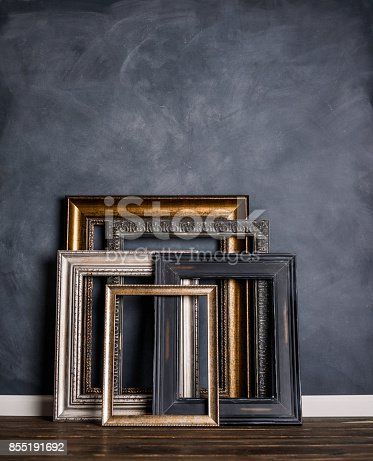 Assortment of empty old picture frames leaning against gray wall