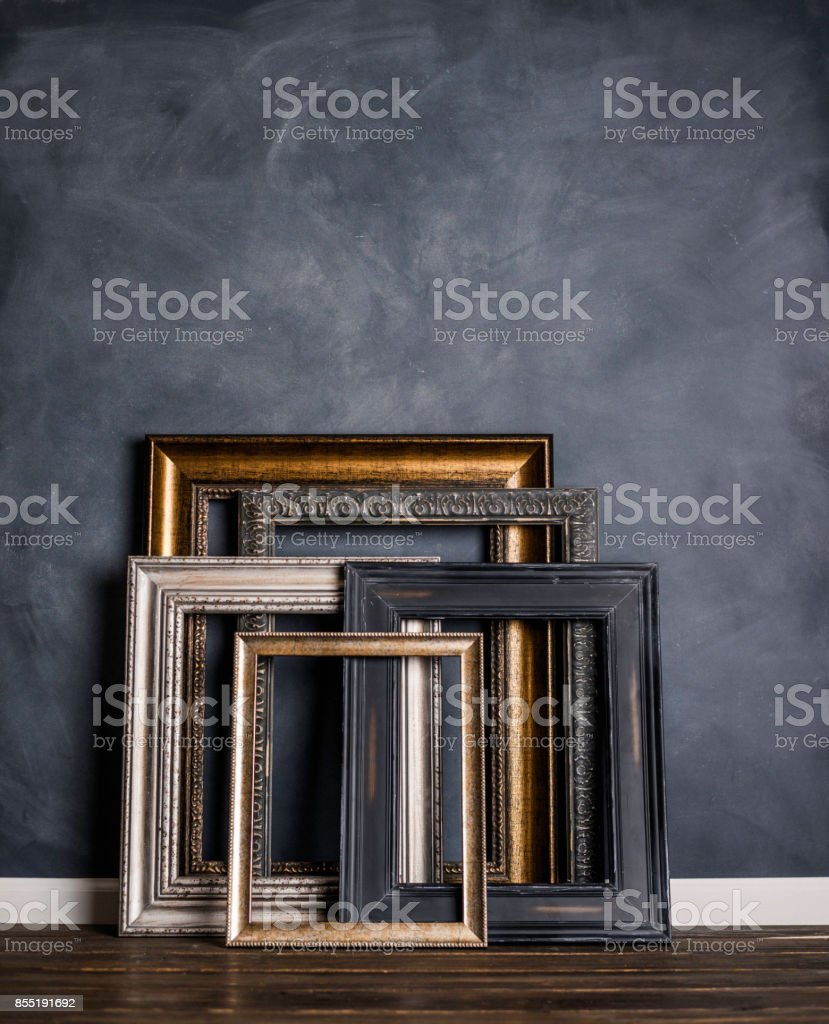 Assortment of empty old picture frames leaning against gray wall stock photo