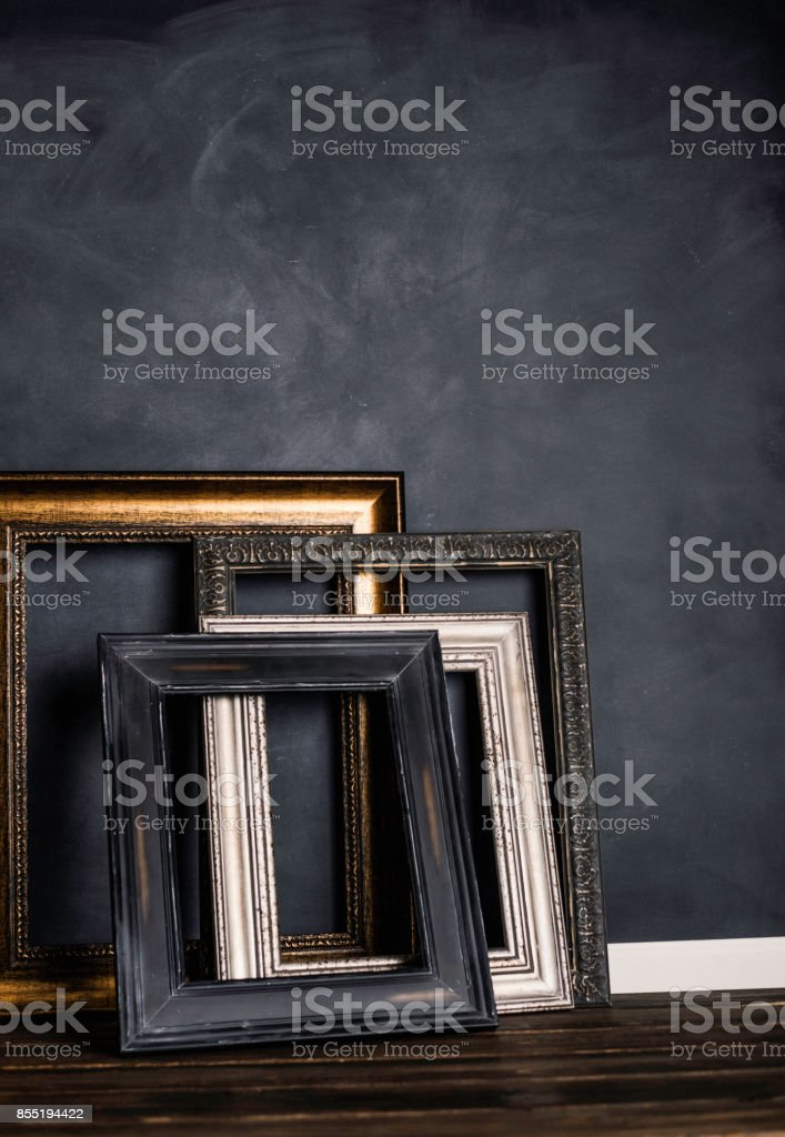 Assortment Of Empty Old Picture Frames Leaning Against Gray Wall ...