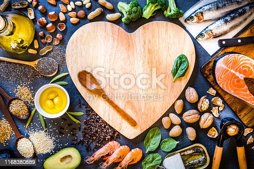 Top view of wooden cutting board with a heart shape surrounded by an assortment of food rich in Omega-3 like various kinds of nuts like hazelnuts, peanuts and almonds, canned and raw fish like salmon and sardine, some heaps of seeds like chia seeds, quinoa and flax seeds, some fruits like avocado and olives, vegetables like spinach and broccoli, and olive oil. The cutting board has a wooden spoon and a spinach leaf but also has a useful copy space on top.  Low key DSLR photo taken with Canon EOS 6D Mark II and Canon EF 24-105 mm f/4L