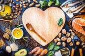 Top view of wooden cutting board with a heart shape surrounded by an assortment of food rich in Omega-3 like various kinds of nuts like hazelnuts, peanuts and almonds, canned and raw fish like salmon and sardine, some heaps of seeds like chia seeds, quinoa and flax seeds, some fruits like avocado and olives, vegetables like spinach and broccoli, and olive oil. The cutting board has a wooden spoon and a spinach leaf but also has a useful copy space on top. \nLow key DSLR photo taken with Canon EOS 6D Mark II and Canon EF 24-105 mm f/4L