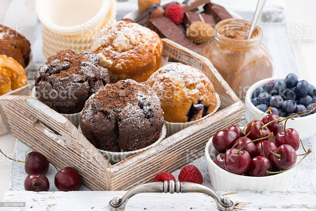 assortment of fresh delicious muffins and berries stock photo