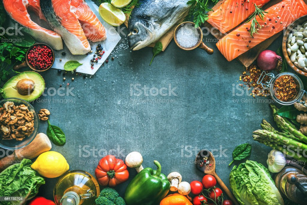 Assortment of fresh fish with aromatic herbs, spices and vegetables stock photo