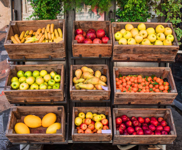 Assortment of fresh fruits and vegetables on market counter in a  wooden boxes Assortment of fresh fruits and vegetables on market counter in a  wooden boxes grocer stock pictures, royalty-free photos & images