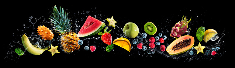 Panoramic wide black background with assortment of fresh fruits and water splashes. High resolution collage for skinali