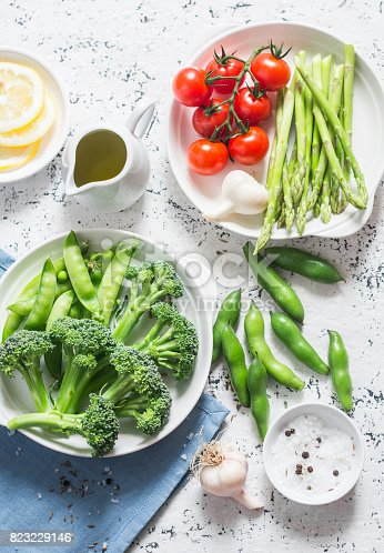 istock Assortment of fresh garden vegetables - asparagus, broccoli, beans, tomatoes,  garlic, green peas on a light background, top view. Vegetarian food concept. Flat lay 823229146