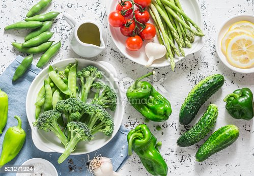 istock Assortment of fresh garden vegetables - asparagus, broccoli, beans, peppers, tomatoes, cucumbers, garlic, green peas on a light background, top view. Vegetarian food concept. Flat lay 821271924