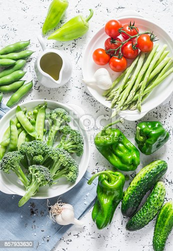 istock Assortment of fresh garden vegetables - asparagus, broccoli, beans, peppers, tomatoes, cucumbers, garlic, green peas on a light background, top view. Vegetarian food concept. Flat lay 857933630