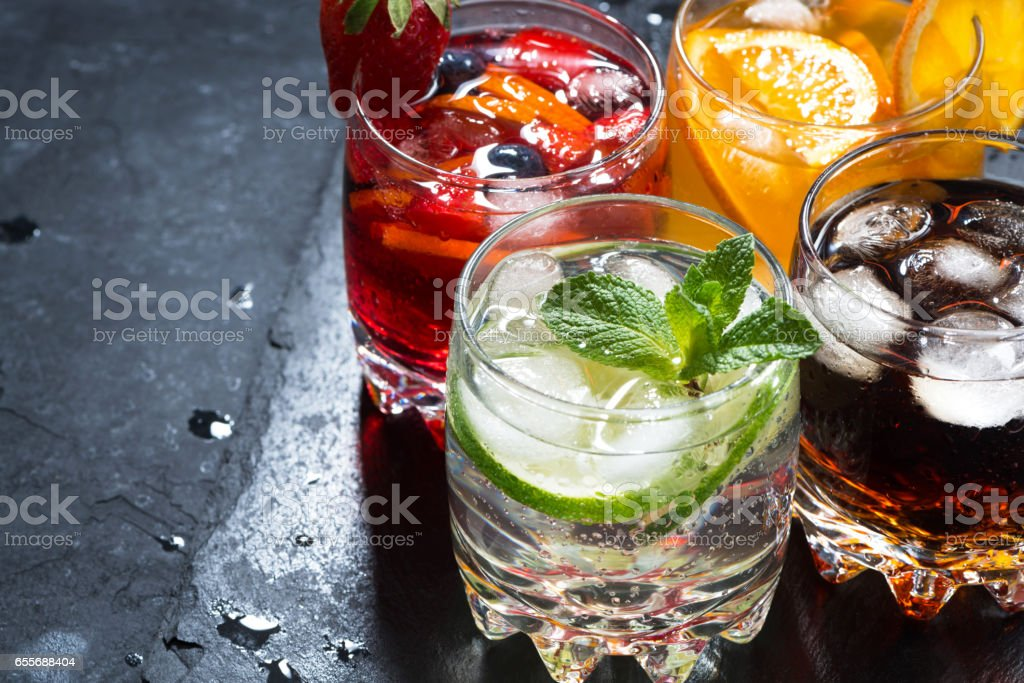 assortment of fresh iced fruit drinks on a black background stock photo