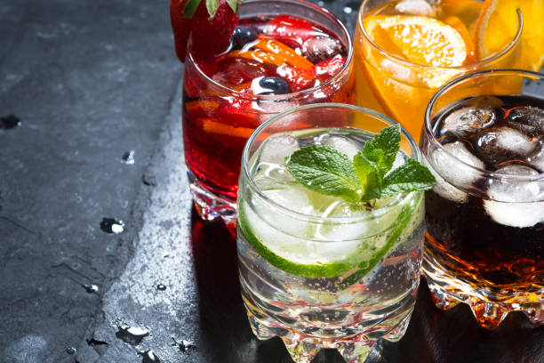 assortment of fresh iced fruit drinks on a black background - cold drink stock photos and pictures