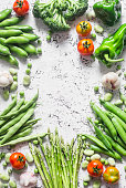 Assortment of fresh organic vegetables with copy space on a light background, top view. Asparagus, broccoli, green beans, peas, beans, peppers, tomatoes, garlic. Healthy vegetarian food concept