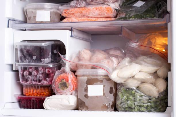variedade de vegetais congelados e bolinhos na geladeira em casa - comida congelada - fotografias e filmes do acervo