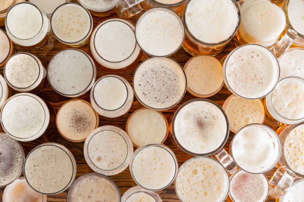 Assortment of full, frothy beer glasses and sizes An assortment of full, frothy beer glasses and sizes on a bar bench top. lager stock pictures, royalty-free photos & images