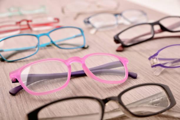 Surtido de gafas en la mesa de madera en una tienda de gafas - foto de stock