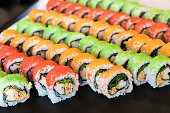 Assortment of healhy multicolored maki sushi rolls. The tasty rolls are very colorful with red, orange and green colored caviar on top, and are filled with salad, fish and crabfish.