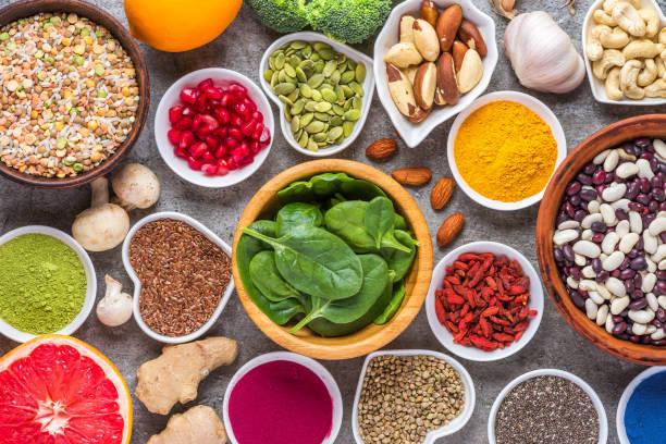 assortiment van gezonde veganistische voedingsmiddelen op concrete achtergrond. superfood. bovenaanzicht - spoorelement stockfoto's en -beelden