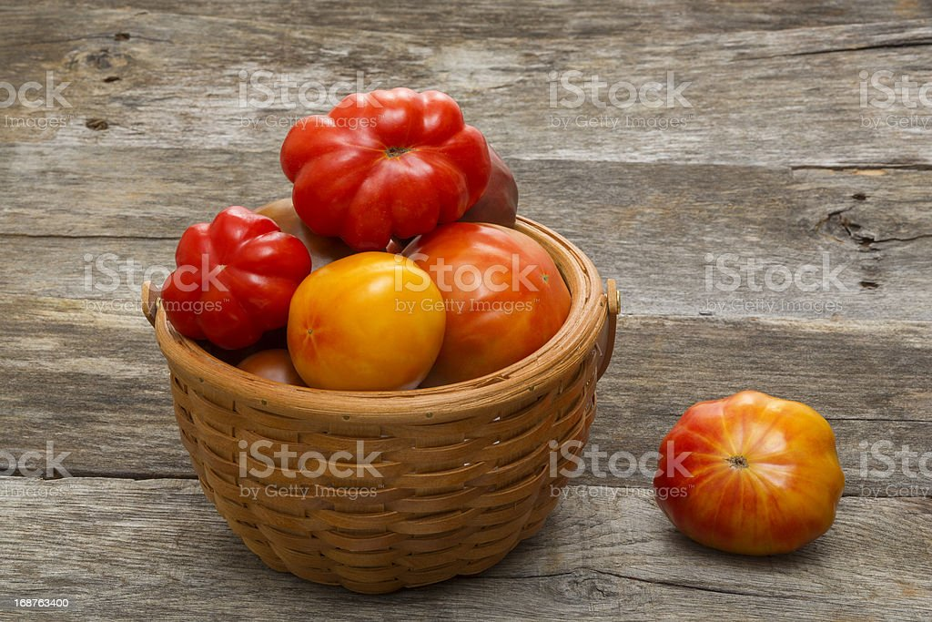 Assortment of Heirloom Tomatoes in Woven Basket royalty-free stock photo