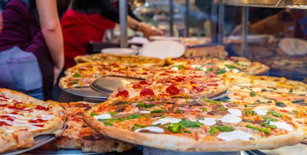 Auswahl an italienischen Pizzas in einem Ladendisplay. Arbeiterinnen, die die Pizzen servieren. – Foto