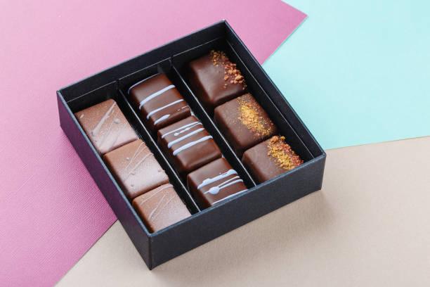 auswahl an luxus-bonbons in box auf bunten lila und blau hintergrund - exklusive mode stock-fotos und bilder
