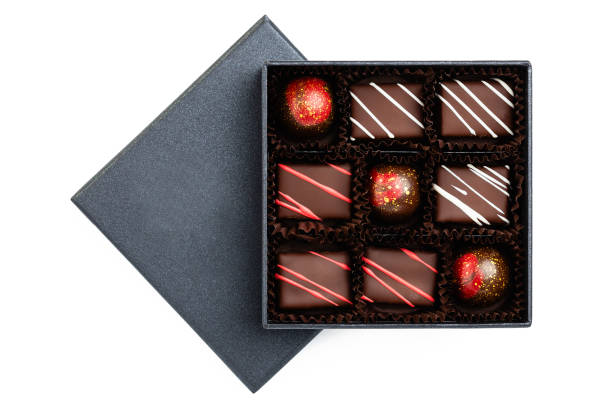 Assortment of luxury bonbons with redl splashes in black box isolated on white background