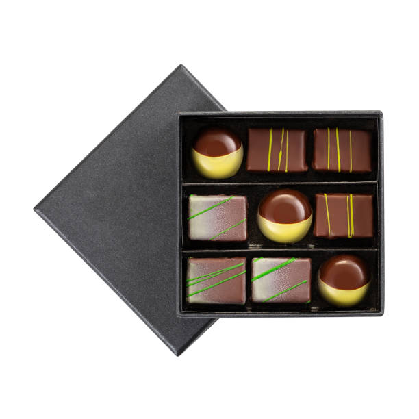 Assortment of luxury chocolate bonbons with green splashes in black box isolated on white background