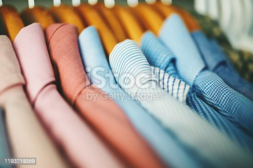 Assortment of mens shirts hanging on wooden coat hangers in a walk in closet
