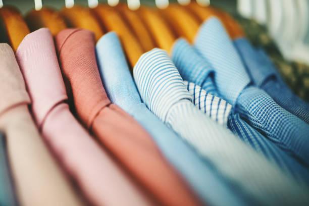 sortiment von herrenhemden auf holzkleiderbügeln - geschäftskleidung stock-fotos und bilder